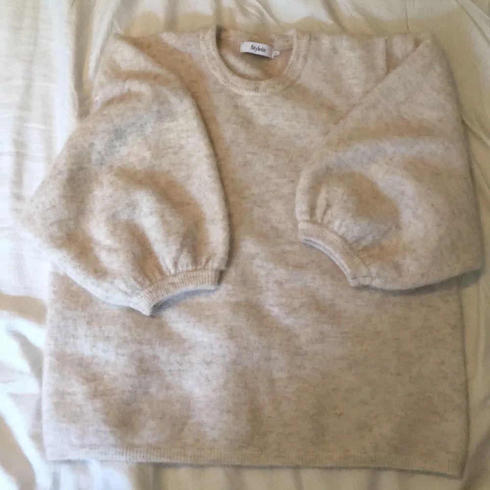 """Cremevit tröja från Stylein. Trekvartslånga """"ballongärmar"""". Mycket mjuk kvalitet - 56% baby alpaca 42% nylon 2% spandex. Köpt för ca. 2 år sedan. Använd ca. 10ggr. Hittar inget att anmärka på såsom fläckar eller tråddragningar. . Stickat."""