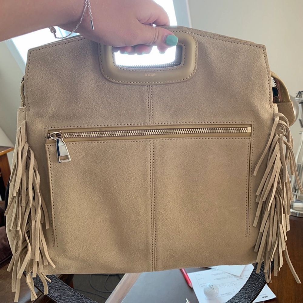 Superfin större beige mocka väska från Maje. Använd få tal gånger. Väskan rymmer jättemycket och är i jättebra skick. Längre axelband i samma färg som väskan medkommer (inte bandet på bilden). Original pris 3690. Väskor.
