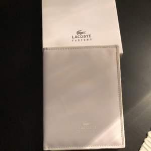 Vit pass holder från Lacoste helt ny fortfarande i plast och kartong. Äkta. Frakt tillkommer. (finns 2)