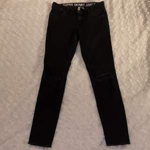 Tighta lågmidjade jeans med hål på knäna (syns dåligt på bild) från H&M, Divided i storlek 34 🖤🖤 Ganska hårda i materialet. Jeansen är i fint skick och är sparsamt använda. Samfraktar gärna med andra plagg och betalning sker via Swish <33