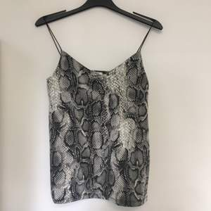 Ormönstrat linne i svart, vitt och grått. Smala spagettiband. Storlek XS men passar S också.