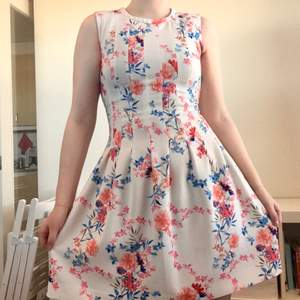 Size 38 dress with length from neck down 88cm. The waist is fitted around ~82cm but should work a few centimetres less as well. Condition is used but is still good quality! The dress has a little stretch in it and is white with Pink, Orange and Blue flowers. The back has a hidden zipper which goes down the back.