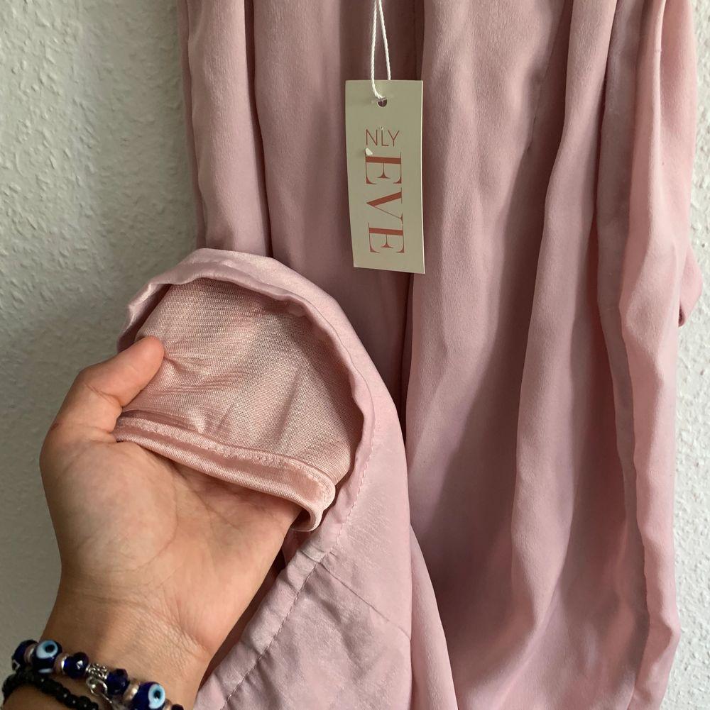 Superfin rosafärgad byxdress från NELLY Eve som jag endast använt en gång. jag har sytt upp benen på jumpsuiten så innerbenslängden är ca 65cm💕 Köparen står för frakt som tillkommer🥰. Övrigt.