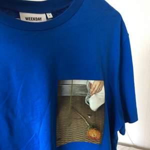 Blå t-shirt med tryck på både framsidan och baksidan från weekday.