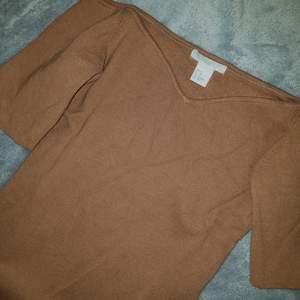 H&M Camel Off The Shoulder Sweater.  Topp, Skick: Som ny, använt 1 gång. (+ 36kr frakt).  * *Short sleeves. Fitted. Size XS. Measured across: shoulder to shoulder 14in, armpit to armpit 13in, waist 11.5in, sleeve 7.5in, length 20in*  Sista bilden är lånad men så ni ser bättre hur toppen ser ut. Den är tjockare i tyget, påminner om bandage tyg. Perfekt till hösten/vintern.
