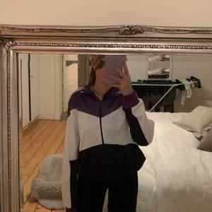 En zip tröja som är lila, vit och svart, köpte den på Beyond retro i somras men använder den inte, skulle säga att det är ett skönt material som liknar materialet på träningströjor, den är lite fodrad också🥰