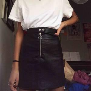 Snygg svart läderkjol (inte äkta) med silvrig dragkedja mitt fram😎 Den sitter väldigt snyggt och  är bra längd på en 32:a eller liten 34:a. Den är i stort sett ny, bara använd en gång. Pris går att diskutera! Möts i Stockholm eller fraktar💙