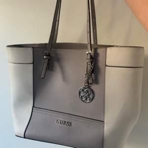Guess väska som har sliten strap men går att använda.