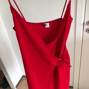 Röd klänning med knyte på framsidan från HM! Storlek 38, använd ca 2 gånger! 60kr