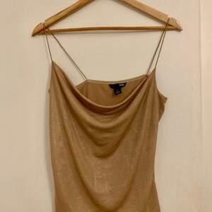 En guldig topp från H&M i cowlneck modell. Toppen är i fint begagnat skick. Storlek M/Medium.