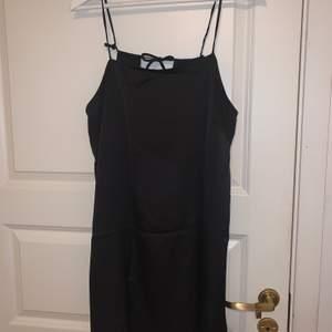 Svart silkesklänning med snygg öppen detalj på baksidan.
