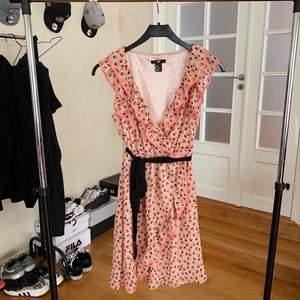 En väldigt söt rosa klänning med svarta prickar och svart band i midjan. Väldigt fint skick - endast använd ett fåtal gånger. Köparen står för frakten.