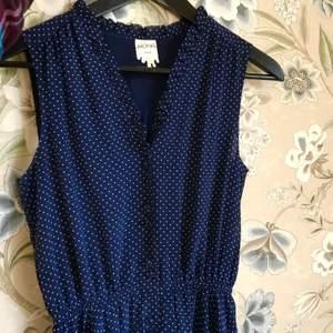Mörkblå klänning med vita prickar från Monki. Söta små knappar klädda i tyg, samt volangdetaljer i v-ringningen. Resor i midjan. Klänningen är aldrig använd och är därmed i perfekt skick!