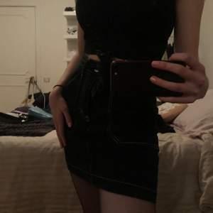 Supersnygg svart kjol med vita sömmar, fickor och knytning!! Knappt använd och i bra skick. Köparen står för frakten 💜