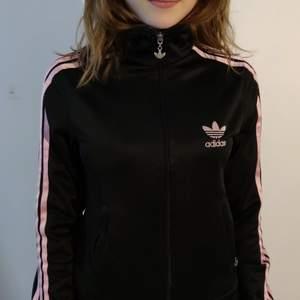 Skit snygg svart adidas jacka med rosa stripes bra skick. Köparen står för frakt