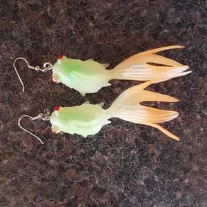 Fiskörhängen. Den gröna delen på fisken är något självlysande i mörkret. Går kanske att ladda upp i ljuset för mer effekt. Säljes då de inte används. Frakt ingår.