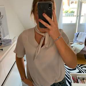 En super classy blus ifrån H&M i en jättefin beige/grå färg med knyte vid halsen som man antingen kan knyta eller ej.💝😋🤠  Hör av dig med eventuella frågor! Köparen står för fraktkostnader💖