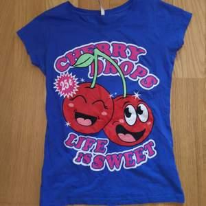 Super söt T-shirt strl S(passar även M och L) med körsbärs tryck på från märket Fishbone. Frakt tillkommer