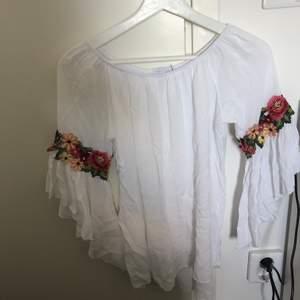 En vit off shoulder topp från Boohoo i väldigt skönt somrigt material. Den består av fina blommiga detaljer längs armbågarna. Säljes på grund av flytt.