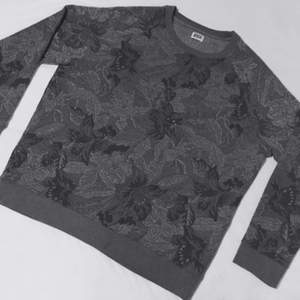 Tjockare god tröja i grtåa toner som sitter lite mer fast och ahr ett insytt mönster utav olika växter/blommor. Som ny!