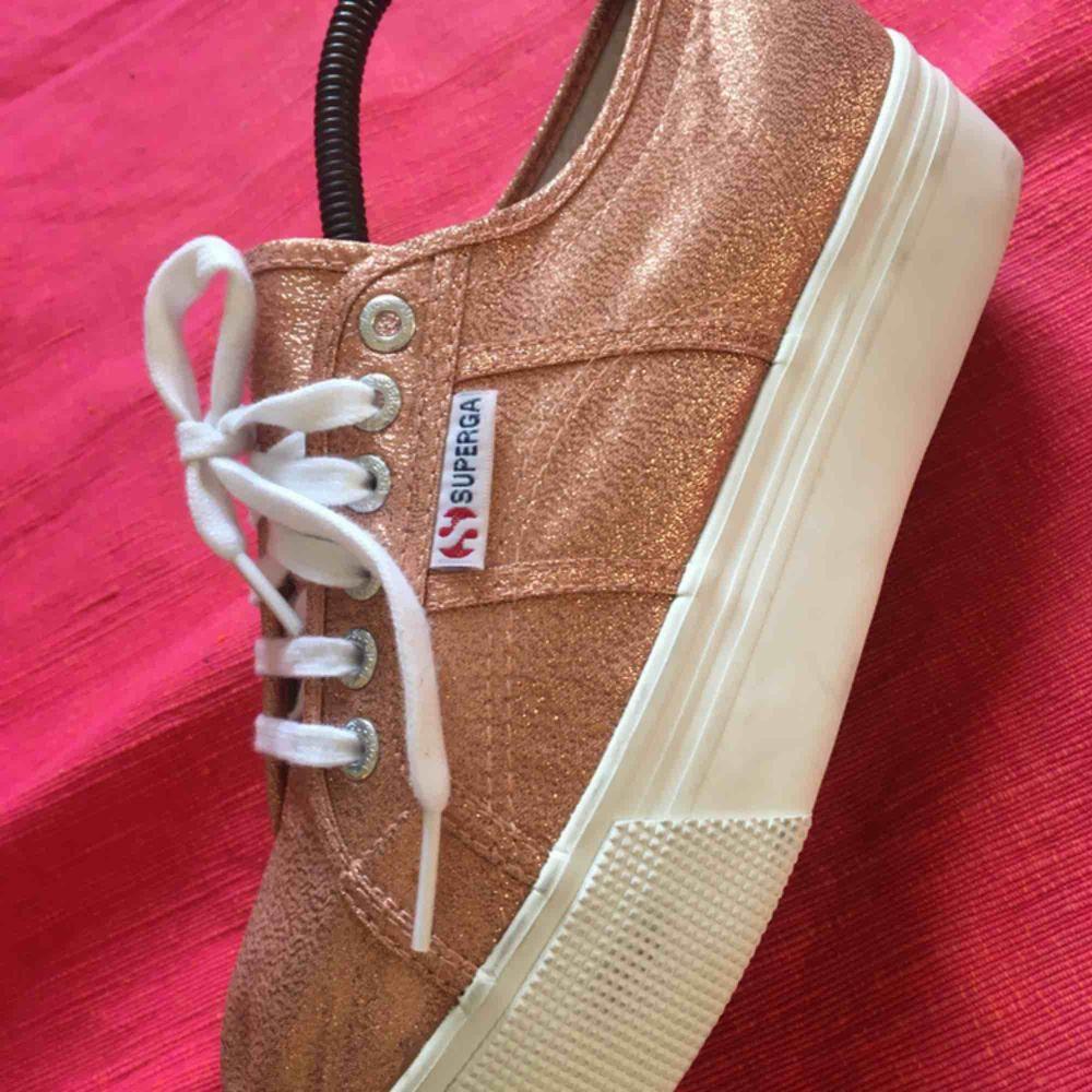 Helt oanvända sneakers med platå från märket Superga. De är bronsfärgat glittriga och riktigt snygga till ett par brunbrända ben i sommar ☀️ 300 plus frakt! . Skor.