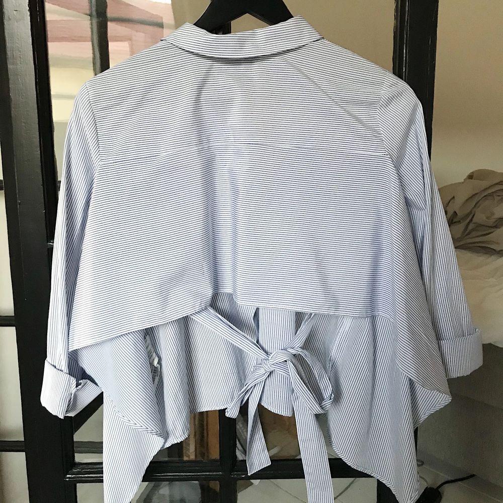 Superfin blå/vit skjorta som är croppad i ryggen med ett knyte. Aldrig använd och inköpt på pull&bear. Storlek S men väldigt flott fit så passar troligen XS-M.. Skjortor.