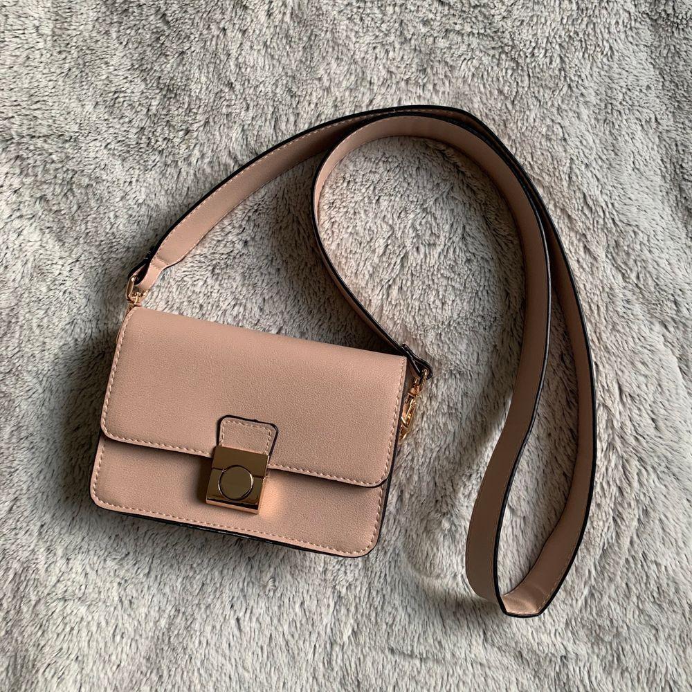 Gammalrosa färgad väska köpt på Åhlens med innerficka. Använd en gång så inga skador alls. Pris inklusive frakt blir 120kr. Väskor.