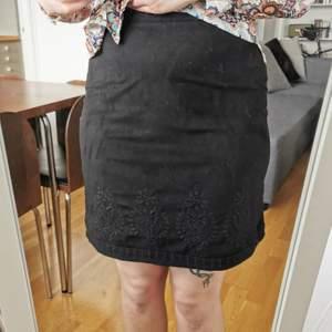 Kjol i mockaimitation med broderier. Strl S. Midjemått 70 cm, längd 51 cm. Dragkedja i sidan. De stora blombroderierna är enbart på framsidan av kjolen, men i över- och nederkant fortsätter broderierna runt hela kjolen. Sparsamt använd, fint skick!