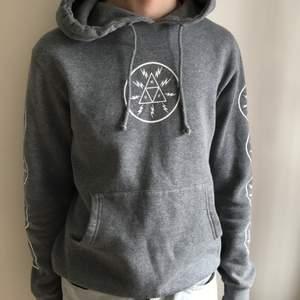 (Herrkläder) Grå hoodie med tryck fram och på båda ärmarna från märket HUF. Bra skick, storlek S.  Frakt tillkommer pris kan diskuteras vid snabb affär