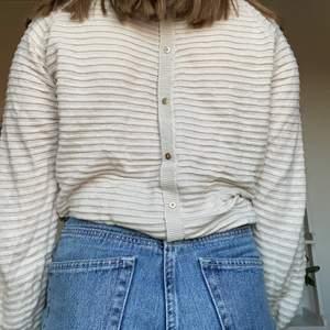 Ribbad beige tröja med knappar bak som detalj. Skön! Inte stickig eller så. Jag har normalt s så tröjan uppskattas till ca M