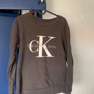 Sweatshirt ifrån Calvin Klein, i en mörkgrå/brunaktig färg. Inköpspris 1000kr. Skick:använt. Ganska stor i storleken.