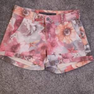 Jeans shorts med rosa och oreange/gula blommor. I väldigt fint skick och knappt använda. Dem har 2 fram fickor. Det går inte att ändra storleken i midjan. Storlek: xs