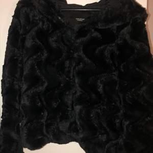 En svart fake päls jacka med stor luva i storlek M men funkar även för storlek S. Använd 1 gång.