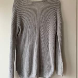 En fin grå stickad tröja med djup rygg i storlek xs från NAKD. Plagget har använts en gång och är därmed i nyskick💕💕