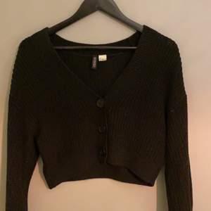 En svart stickad tröja med knappar, köpt på H&M. Bra skick. Köparen står för frakt!