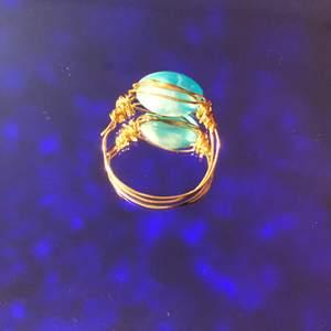Hemmagjord ring med en blåvit pärla och ringmatralet är i färgen guld( inte äkta) . Fin att ha till t.ex. fina middagar eller i din vardag.