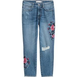 light wash ripped jeans with flower embroidery. in basically new condition, but are missing one belt loop at the back