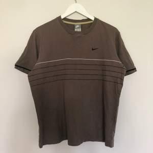 En vintage nike t-shirt med en mini swoosh. Tröjan är i populär brun färg som under den senaste blivit väldigt trendig. Tishan har 5 streck som går över den. Den är i vintage skick och har inga defekter. Storlek Large.