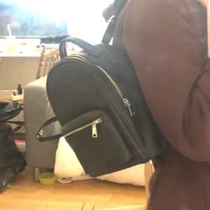 En liten svart ryggsäck. Har justerbara band. Aldrig använd, väldigt bra skick