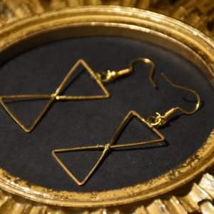 Guldiga örhängen med nickelfria krokar.