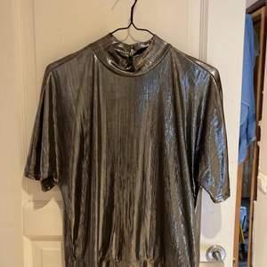 Silvrig tröja med öppen rygg perfekt till nyår. Använd vid ett tillfälle.