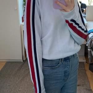 Säljer denna vita hollister tröja med röd, vit och svarta ränder på ärmarna. Läs gärna bio innan köp