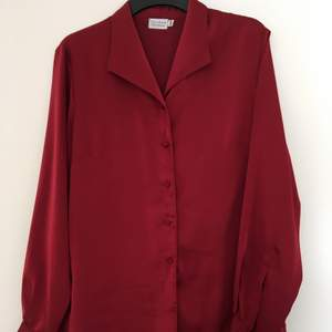Mörk röd blus i glänsande silkesliknande material. Sparsamt använd.