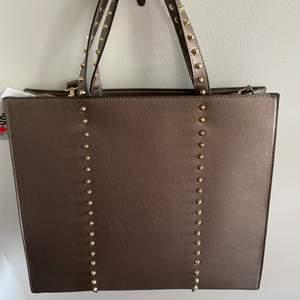 Säljer denna fina helt nya bruna väskan med små nitar på. Köptes nyss och aldrig använd. Köparen står för frakt