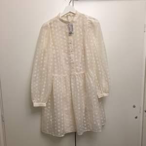 Helt ny vit klänning från H&M med prislappen kvar. En prickig vit klänning med en rosa underklänning som sitter fast med klänningen. Storlek XS men är stor i storleken och passar därför M skulle jag säga. Frakten ingår inte