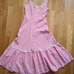 Klänning från 50 talet i topp skick. Ljust rosa och vit rutig. Fler bilder kan självklart fås.. Storlek 34. Klänningen är i riktigt fint skick. 1000kr ink spårbart frakt