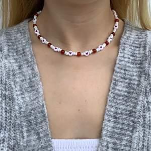 Vitt pärlhalsband med röda hjärtan och röd/orangea pärlor❤️🧡🤍 halsbandet försluts med lås och tråden är elastisk