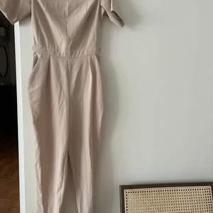 Snygg tredig jumpsuit i ljus beige färg, storlek 6, XS från spotlight warehouse. Från djur och rökfritt hem