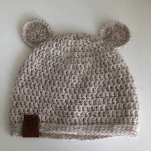 """Supersöt handvirkad teddy-mössa🧸, virkad av mjukt garn. Finns för barn mellan 0 och 12 månader!🥰 Skicka mått runt huvud och vilken initial du vill ha på """"lappen"""" till mig om du vill beställa en mössa!💞 Exempel på initial finns på bild två😊"""