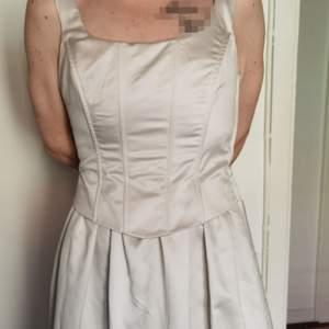 Säljer denna Silvergrå klänning som endast är använd 1 gång på väninnans bröllop, det är först till köp som gäller och priset är diskuterbart.   Lätt och elegant, faller snyggt. Längden på klänningen från axlarna är 137 cm, från dragkedjan är den 93 cm.  Drakedja i sidan och korsett snörningen går att reglera. Finns även en snygg cape som följer med, den är längre på sidorna och kortare i bak, knäpps i halsen.  Finns i Kallebäck eller skickas om köpare betalar spårbar frakt på 99 kronor.